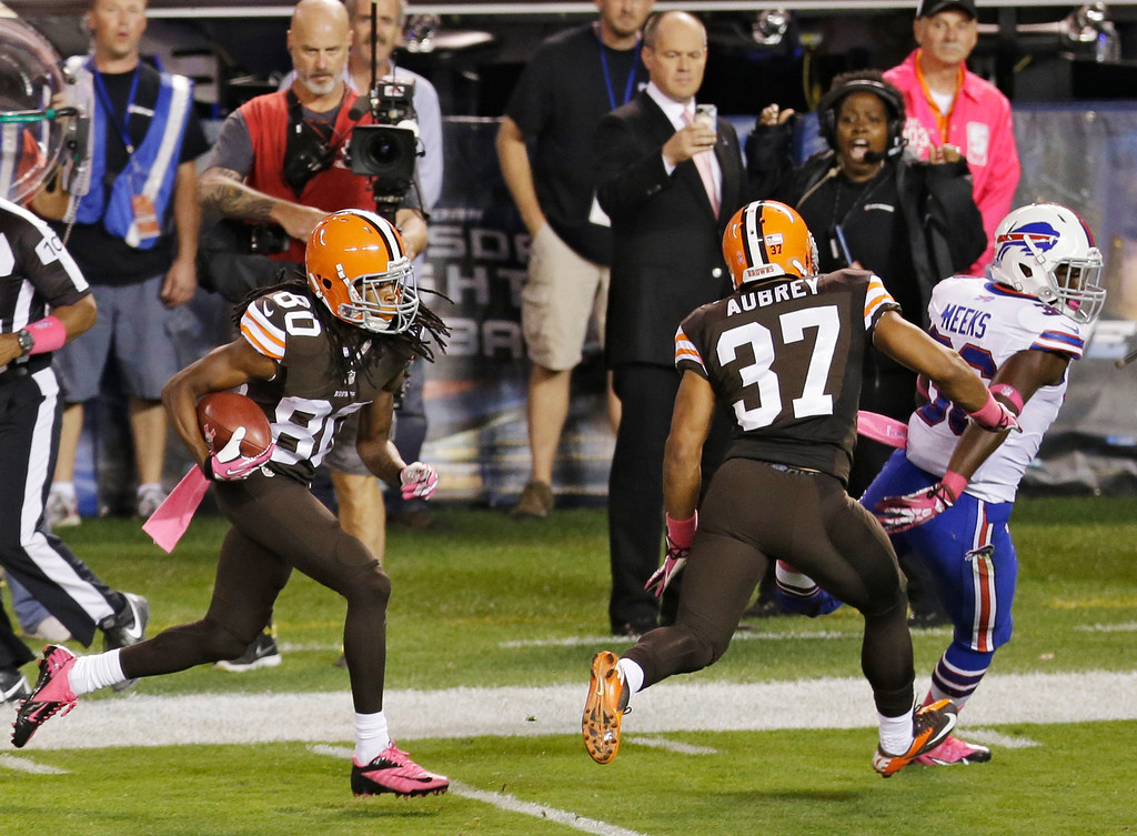 Description of . Cleveland Browns' Travis Benjamin (80) returns a punt 79 yards for a touchdown against the Buffalo Bills in the second quarter of an NFL football game Thursday, Oct. 3, 2013, in Cleveland. Browns' Josh Aubrey (37) seals off Bills' Jonathan Meeks to spring Richardson. (AP Photo/Tony Dejak)