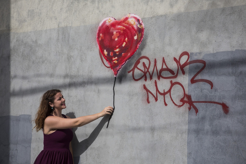Description of . A woman poses with a piece of street art, which depicts a heart-shaped balloon covered in bandages and was allegedly done by the street artist Banksy, on October 7, 2013 in the Red Hook neighborhood of the Brooklyn borough of  New York City. The piece was defaced with red spray paint shortly after being completed.  (Photo by Andrew Burton/Getty Images)