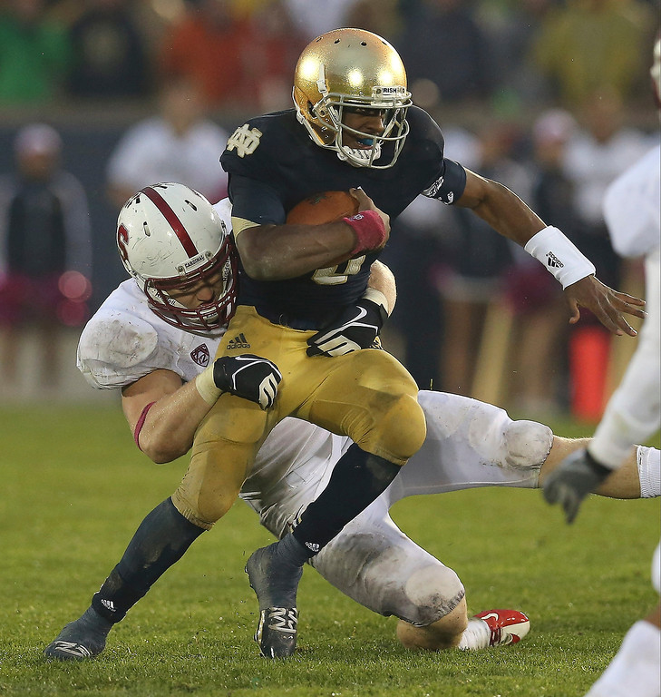 Description of . Everett Golson #5 of the Notre Dame Fighting Irish tries to break away from Henry Anderson #91 of the Standford Cardinal at Notre Dame Stadium on October 13, 2012 in South Bend, Indiana. Notre Dame defeated Stanford 20-13 in overtime.  (Photo by Jonathan Daniel/Getty Images)