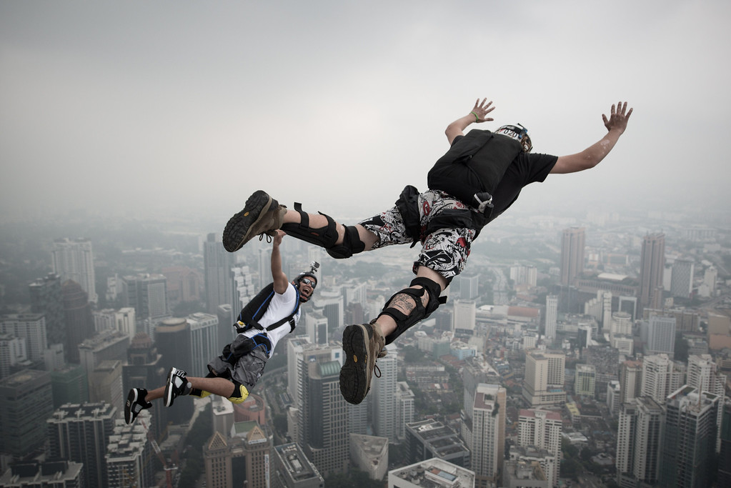 Description of . Base jumper David Laffargue (R) and Rodolphe Roger Coianiz (L) from France leap from the 300-meters Open Deck of the Malaysia's landmark Kuala Lumpur Tower during the International Tower Jump in Kuala Lumpur on September 27, 2013. AFP PHOTO / MOHD RASFAN/AFP/Getty Images