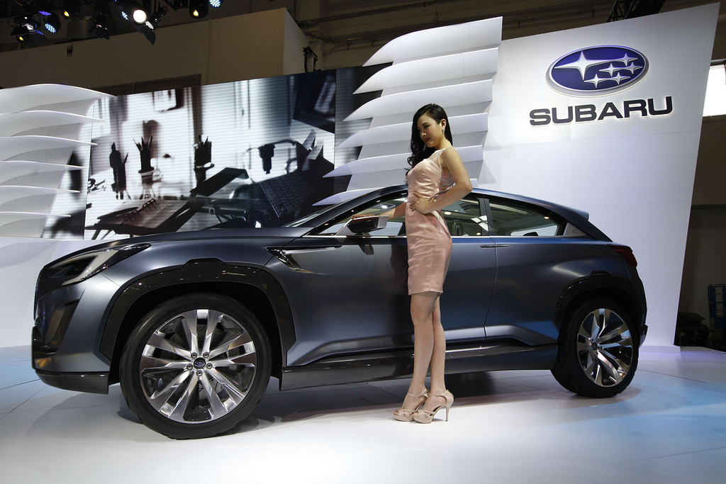 Description of . A model poses by a Subaro car at the China International Exhibition Center new venue during the