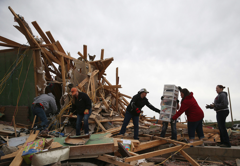 Description of . Volunteers help clean debris at the site of a home that was detroyed when a tornado hit the area, April 29, 2014 in Vilonia, Arkansas. Deadly tornadoes ripped through the region April 27, leaving more than a dozen dead.  (Photo by Mark Wilson/Getty Images)