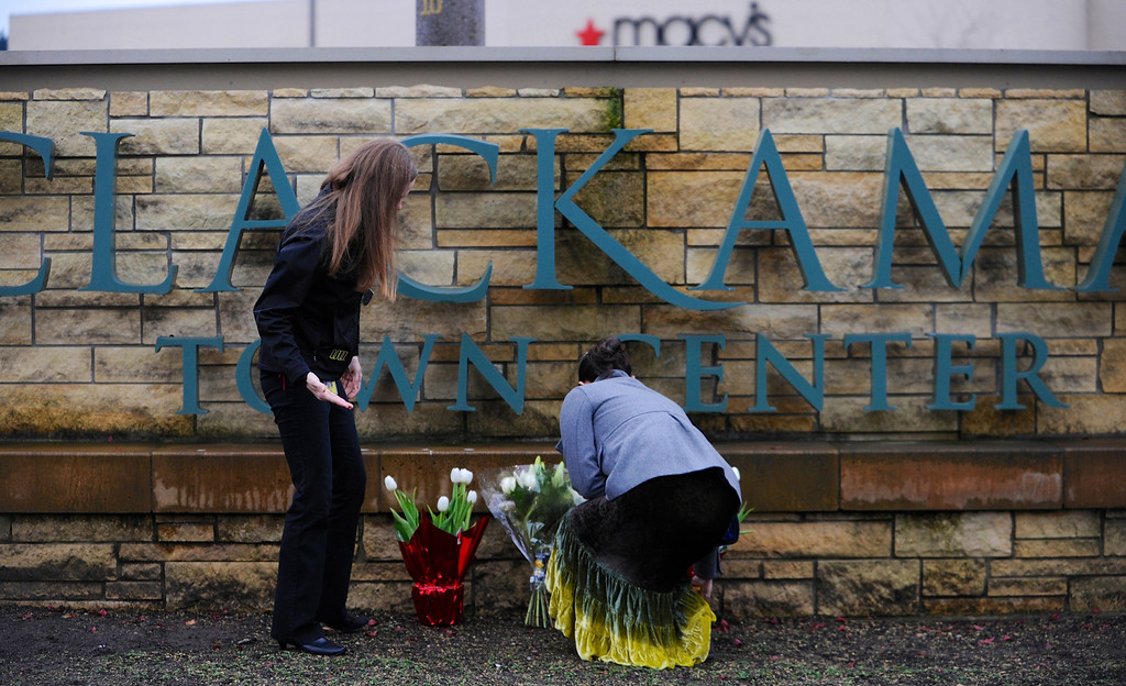 Description of . Leslie King, right and Tenille Beseda place flowers Wednesday Dec. 12, 2012, at the entrance to the scene of a multiple shooting yesterday at Clackamas Town Center Mall in Clackamas, Ore.  A gunman who opened fire on shoppers at a Portland mall had no connection to the two people he fatally shot and wanted to kill as many people as possible, police said Wednesday. (AP Photo/Greg Wahl-Stephens)