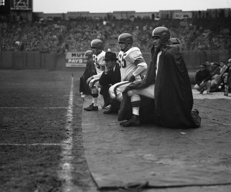 Description of . Cleveland Browns coach Paul Brown is pictured on Dec. 8, 1953, during a game against the Cardinals. From left to right are Ray Renfro, halfback; Brown; Chuck Noll, guard; and Billy Reynolds, halfback. Location is not known. (AP Photo)