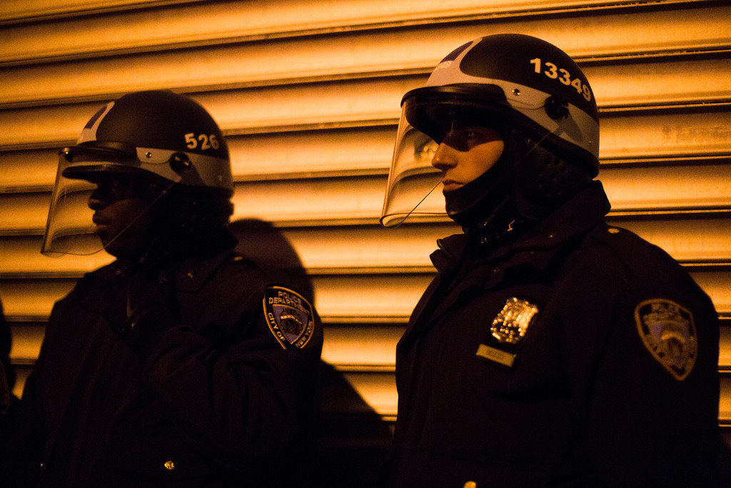 Description of . NYPD crowd control officers keep watch on a march of demonstrators as they protest against the shooting of Kimani