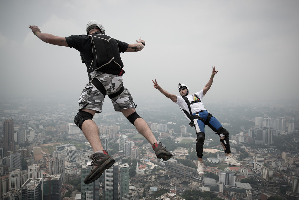 Description of . Base jumper Vladimir Spigler (L) and Ivan Colella from Italy leap from the 300-metres Open Deck of the Malaysia's landmark Kuala Lumpur Tower during the International Tower Jump in Kuala Lumpur on September 27, 2013. Some 103 professional base jumpers from 20 countries are taking part in the annual event. AFP PHOTO / MOHD RASFANMOHD RASFAN/AFP/Getty Images