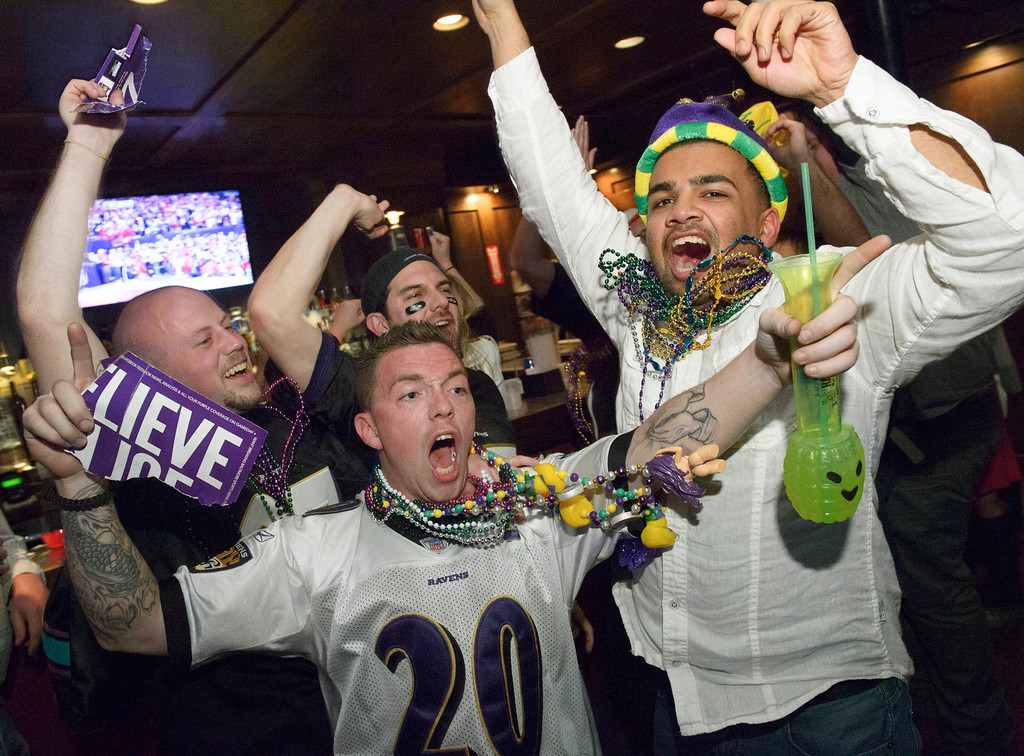 Description of . Lee Fuller, of Baltimore, center, and others celebrate the Baltimore Ravens winning the Super Bowl at the Famous Door Bar as fans of the Ravens and San Francisco 49ers NFL football teams pack the French Quarter on Bourbon Street for Super Bowl XLVII in New Orleans, Sunday, Feb. 3, 2013. (AP Photo/Matthew Hinton)