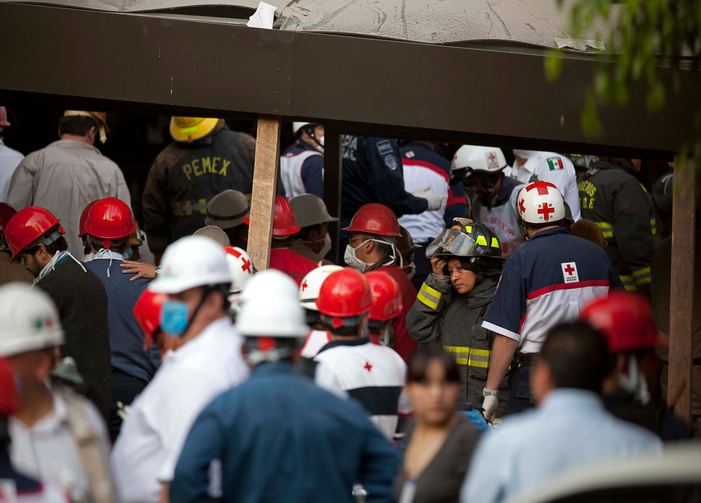 Description of . Rescue workers and firefighters gather at the site of an explosion at an adjacent building to the executive tower of Mexico's state-owned oil company PEMEX, in Mexico City, Thursday Jan. 31, 2013.  (AP Photo/Eduardo Verdugo)