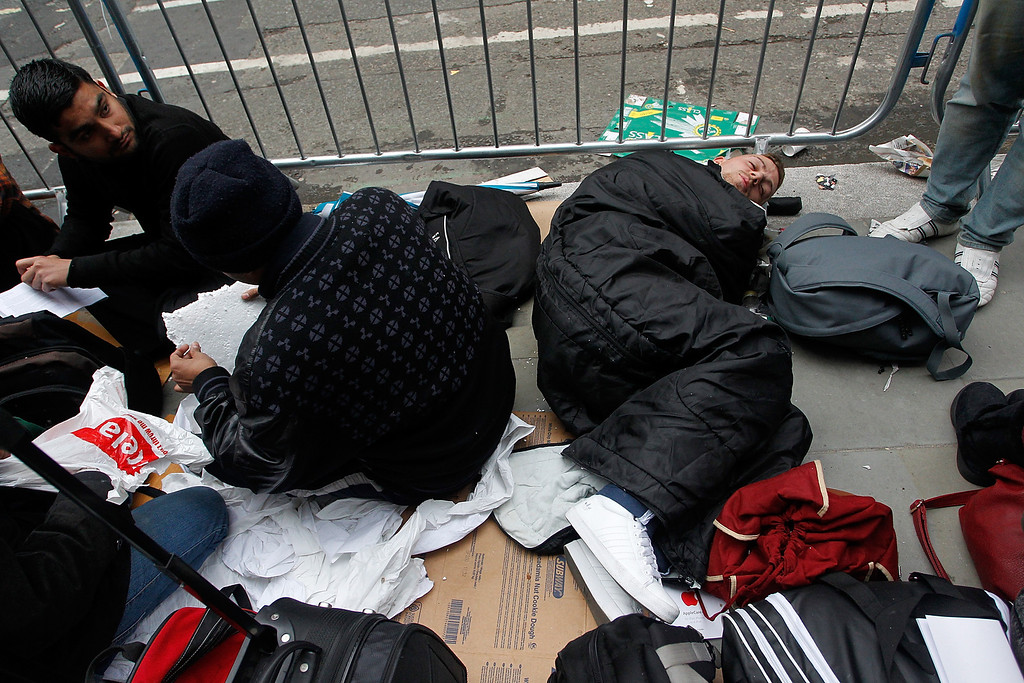 Description of . People sleep on the floor as they queue for iPhone 5S at Regent Street on September 20, 2013 in London, England. Some consumers have queued for five days, sleeping in makeshift tents, to be the first to own the new updated iPhone. (Photo by Mary Turner/Getty Images)