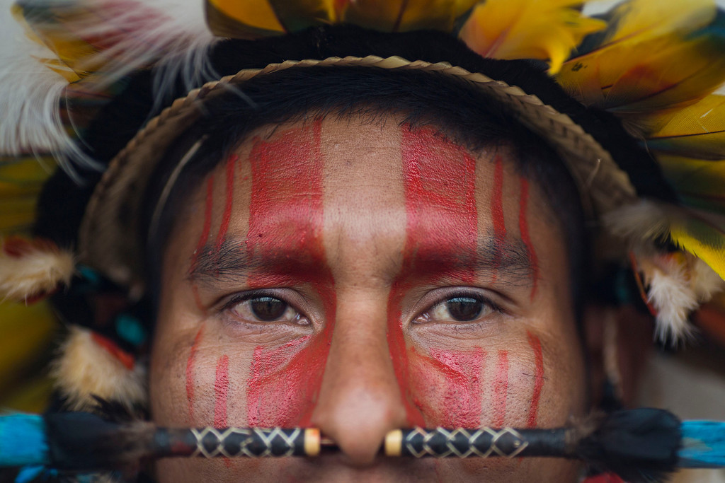 Description of . A Rikbaktsa Indian watches the bow and arrow competition during the indigenous games in Cuiaba, Brazil, Tuesday, Nov. 12, 2013.  (AP Photo/Felipe Dana)