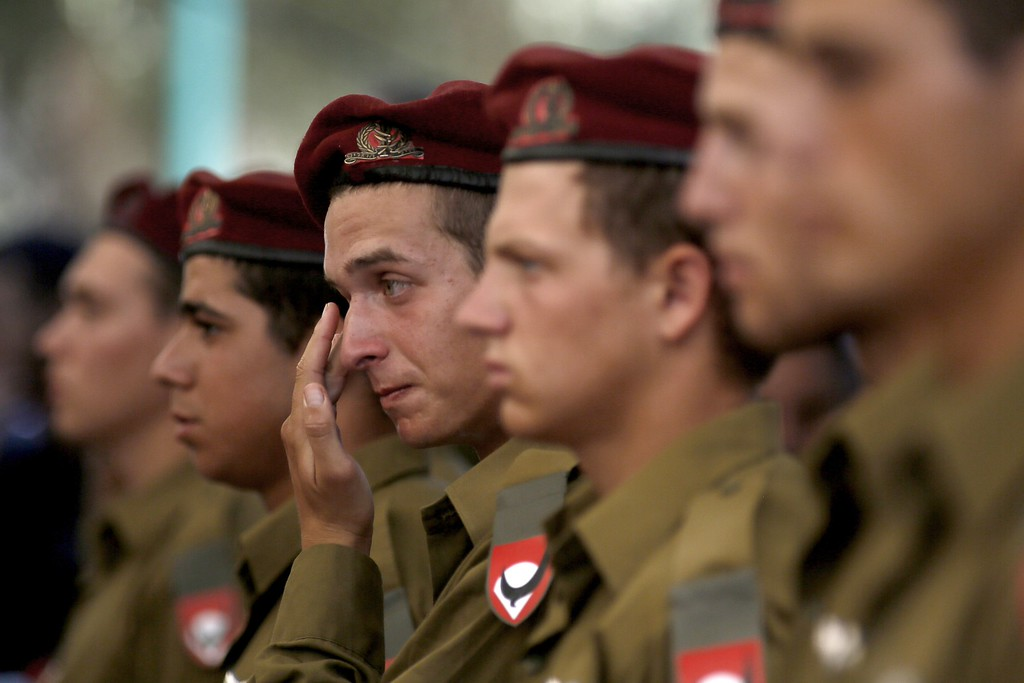 Description of . Comrades of 20-year-old Israeli  St.-Sgt. Guy Algranati, mourn during his funeral in the military section of the Kiryat Shaul cemetery in Tel Aviv on July 31, 2014, after he was killed the previous day in combat in the Gaza Strip.  Israel said it would not pull troops from Gaza until they finish destroying a network of cross-border tunnels, and the army confirmed mobilising another 16,000 additional reservists, hiking the total number called up to 86,000. AFP PHOTO/ GALI TIBBON/AFP/Getty Images