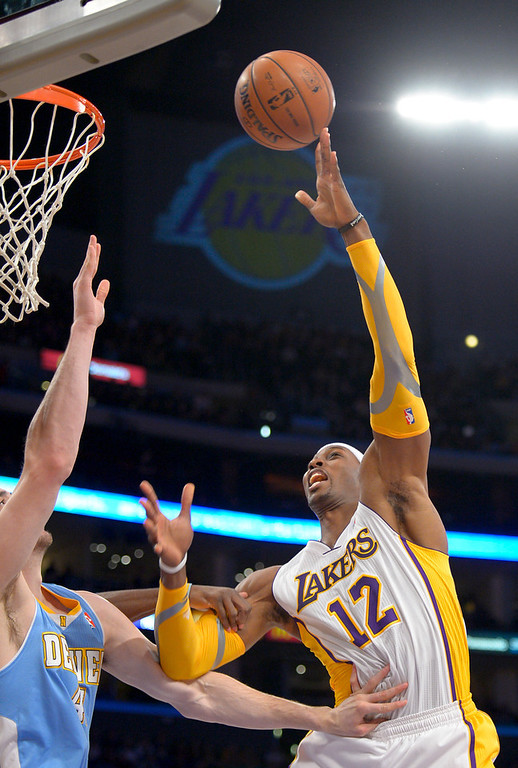 Description of . Los Angeles Lakers center Dwight Howard, right, shoots over Denver Nuggets' Kosta Koufos during the first half of their NBA basketball game, Sunday, Jan. 6, 2013, in Los Angeles. (AP Photo/Mark J. Terrill)