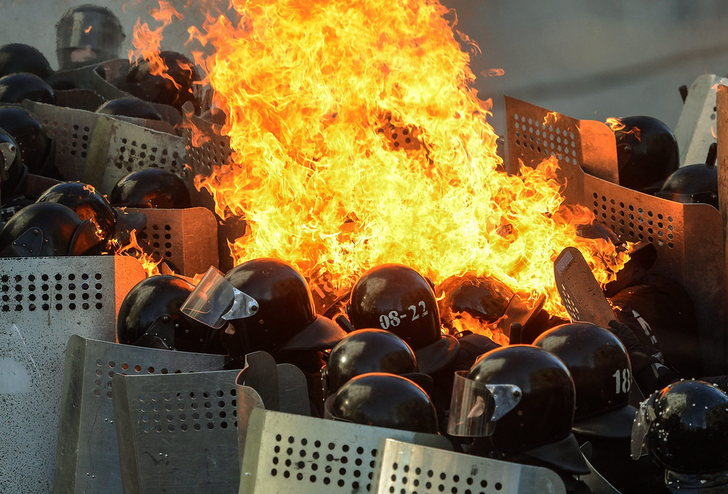 Description of . Riot policemen in flames clash with protesters during the continuing protest in downtown Kiev, Ukraine, 18 February 2014. A least three protesters were killed in clashes with police on 18 February, Ukrainian opposition activists say.  EPA/ANDREW KRAVCHENKO