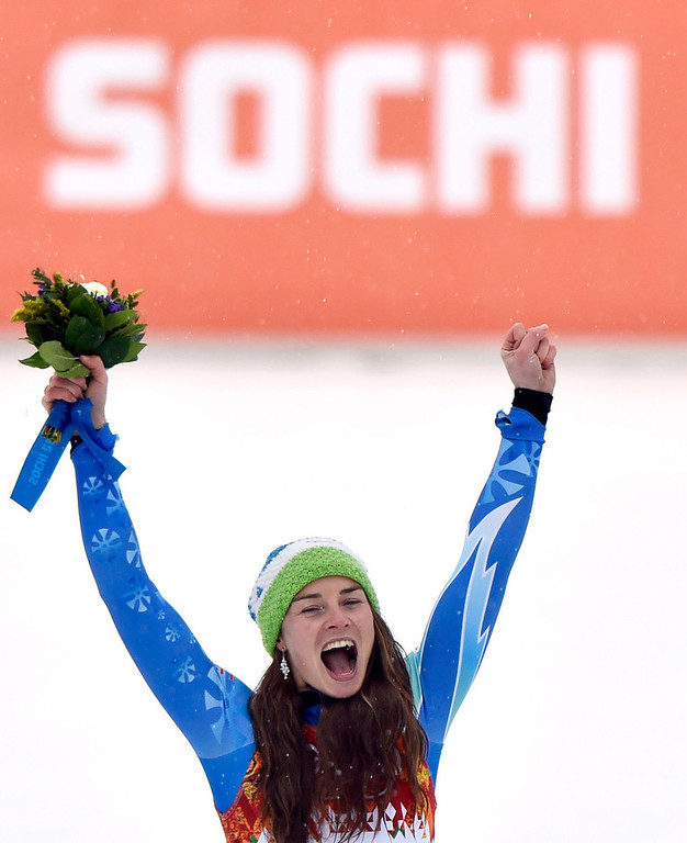 Description of . Tina Maze of Slovenia celebrates her gold medal during the flower ceremony for the Women's Giant Slalom at the Rosa Khutor Alpine Center at the Sochi 2014 Olympic Games, Krasnaya Polyana, Russia, 18 February 2014.  EPA/HANS KLAUS TECHT