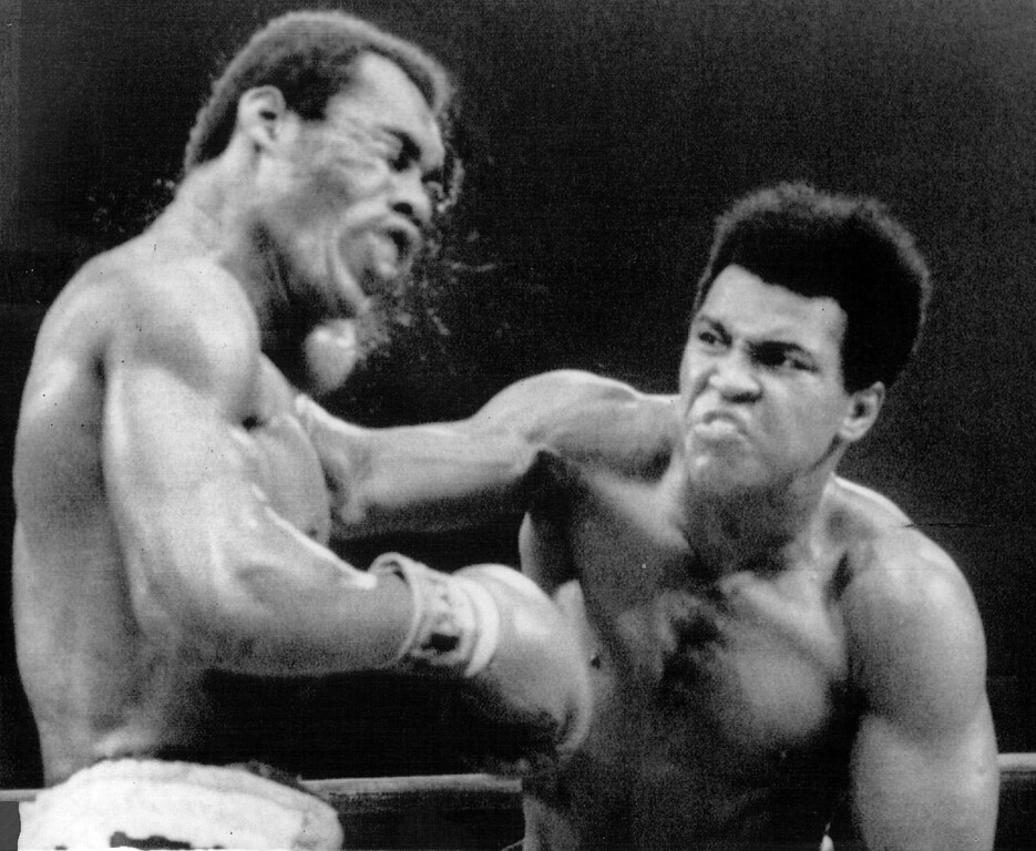 Description of . Muhammad Ali crashes a right to the side of Ken Norton's head during a middle round of their 12-round re-match at the Forum in Inglewood, Calif., 1973. Denver Post Library photo archive
