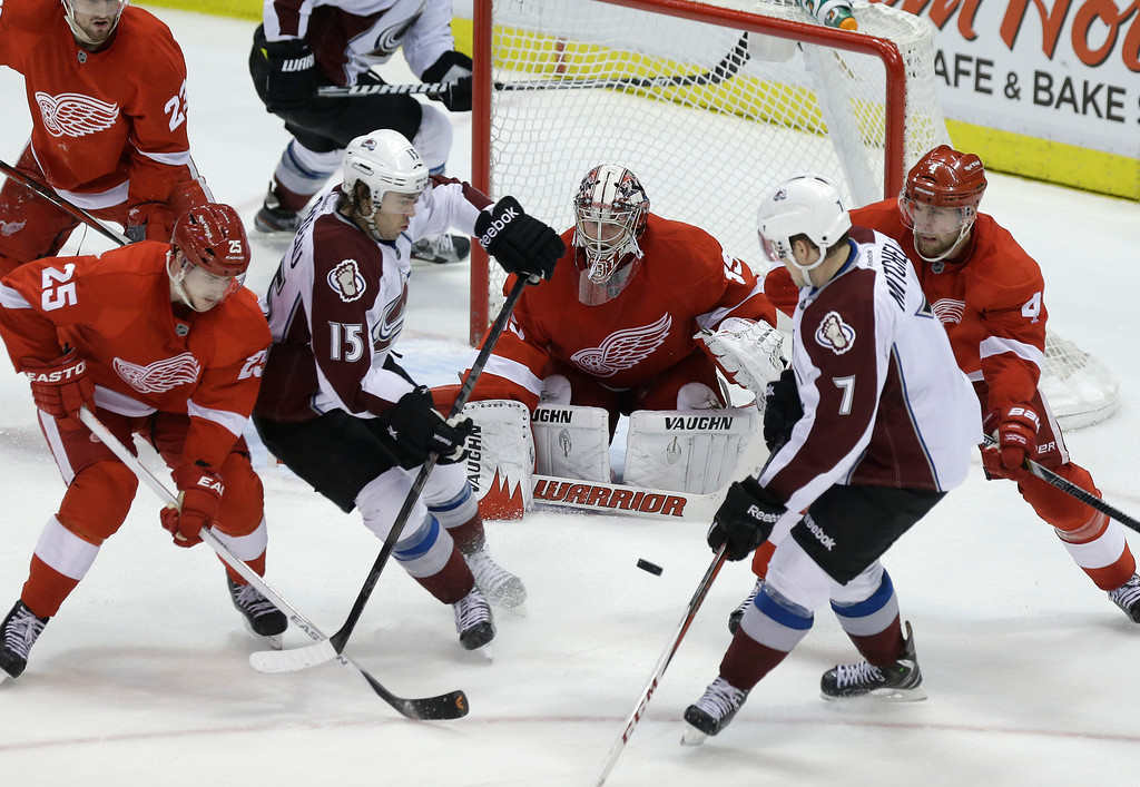 Description of . Detroit Red Wings center Cory Emmerton (25) and defenseman Jakub Kindl (4), of the Czech Republic, defend Colorado Avalanche right wing P.A. Parenteau (15) and center John Mitchell (7) in front of Detroit goalie Jimmy Howard (35) during the third period of an NHL hockey game in Detroit, Tuesday, March 5, 2013. Detroit won 2-1. (AP Photo/Carlos Osorio)