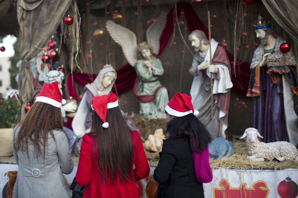 Description of . BETHLEHEM, WEST BANK - DECEMBER 25: People look at a Nativity scene of the birth of Jesus, outside the Church of the Nativity, traditionally believed to be the birthplace of Jesus Christ, on December 25, 2013 in Bethlehem, West Bank.  Every Christmas pilgrims travel to the church where a gold star embedded in the floor marks the spot where Jesus was believed to have been born. (Photo by Oren Ziv/Getty Images)