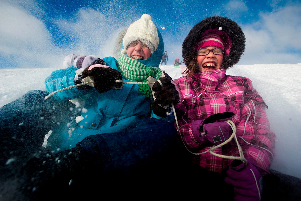 Description of . Emily Dresbach, left, 12, and Kelsey Blum, 11, sled down the hill on Thursday, Dec. 20, 2012 at Holmes Lake in Lincoln, Neb. (AP Photo/The Journal-Star, Adam Wolffbrandt) LOCAL TV OUT; KOLN-TV OUT; KGIN-TV OUT; KLKN-TV OUT
