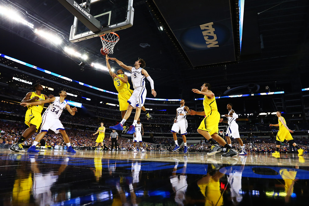 Description of . ARLINGTON, TX - MARCH 29:  Jeff Withey #5 of the Kansas Jayhawks blocks a shot by Trey Burke #3 of the Michigan Wolverines in the second half during the South Regional Semifinal round of the 2013 NCAA Men\'s Basketball Tournament at Dallas Cowboys Stadium on March 29, 2013 in Arlington, Texas.  (Photo by Tom Pennington/Getty Images)