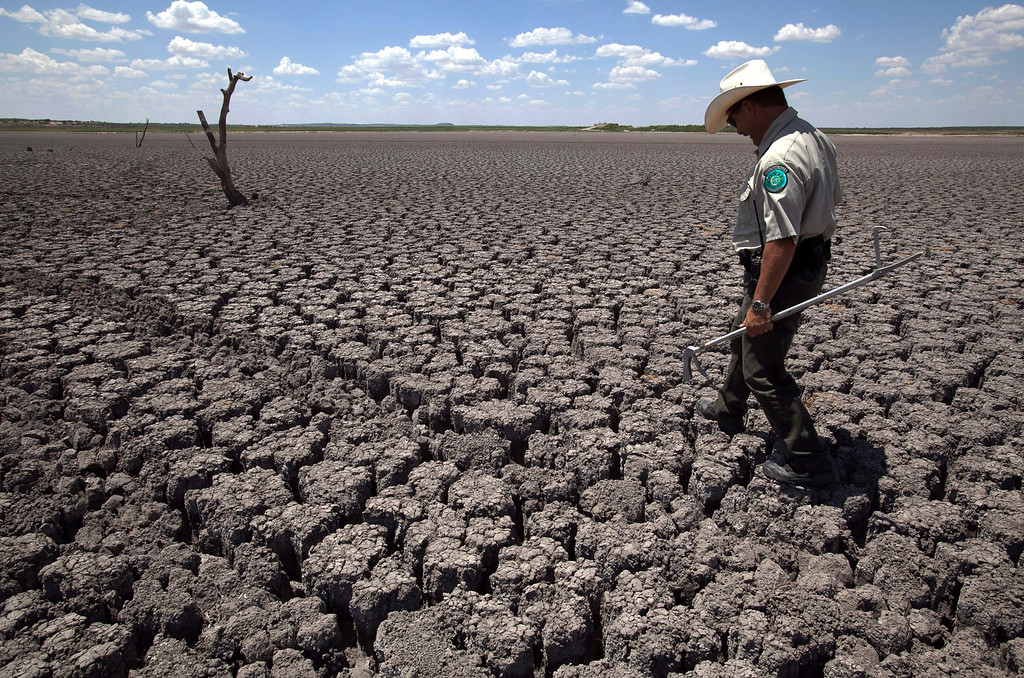 Description of . In this Aug. 3, 2011 file photo, Texas State Park police officer Thomas Bigham walks across the cracked lake bed of O.C. Fisher Lake in San Angelo, Texas.  (AP Photo/Tony Gutierrez)