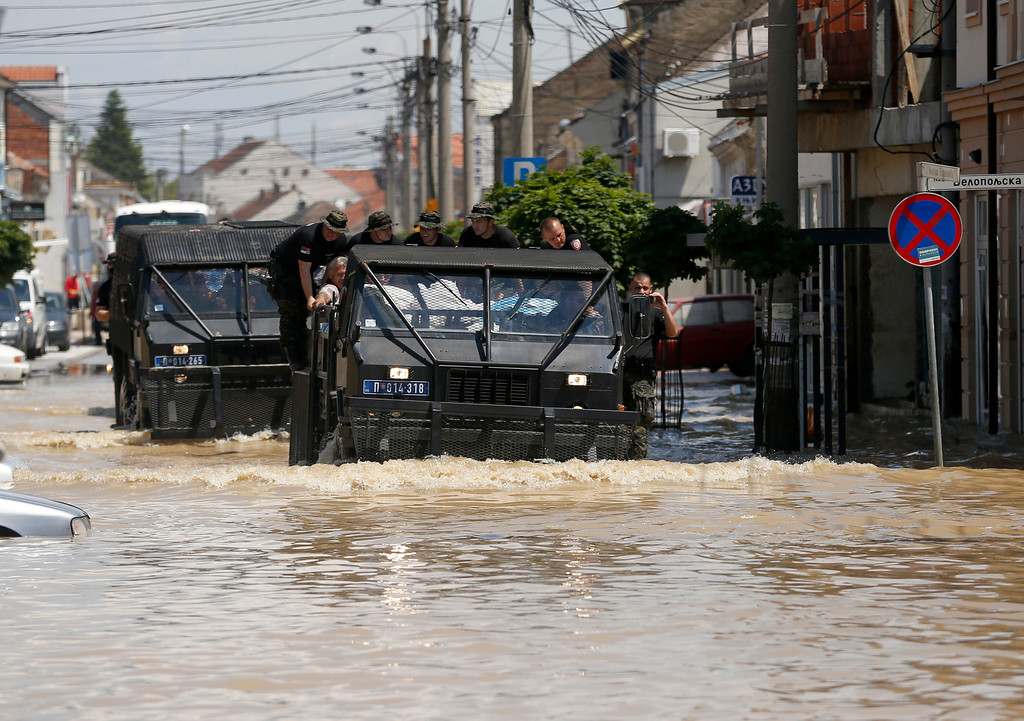 Description of . A police vehicle drives through flooded street in Obrenovac, some 30 kilometers (18 miles) southwest of Belgrade, Serbia, Tuesday, May 20, 2014. Serbia, Bosnia and Croatia have been hit by the worst flooding in more than 100 years, forcing half a million people out of their homes and leading to more than three dozen deaths. (AP Photo/Darko Vojinovic)