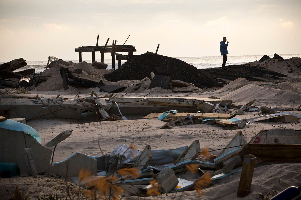 Description of . A man smokes a cigarette while surveying the damage caused by Hurricane Sandy, in the Ortley Beach area of Toms River, New Jersey November 28, 2012. The storm made landfall along the New Jersey coastline on October 29. REUTERS/Andrew Burton