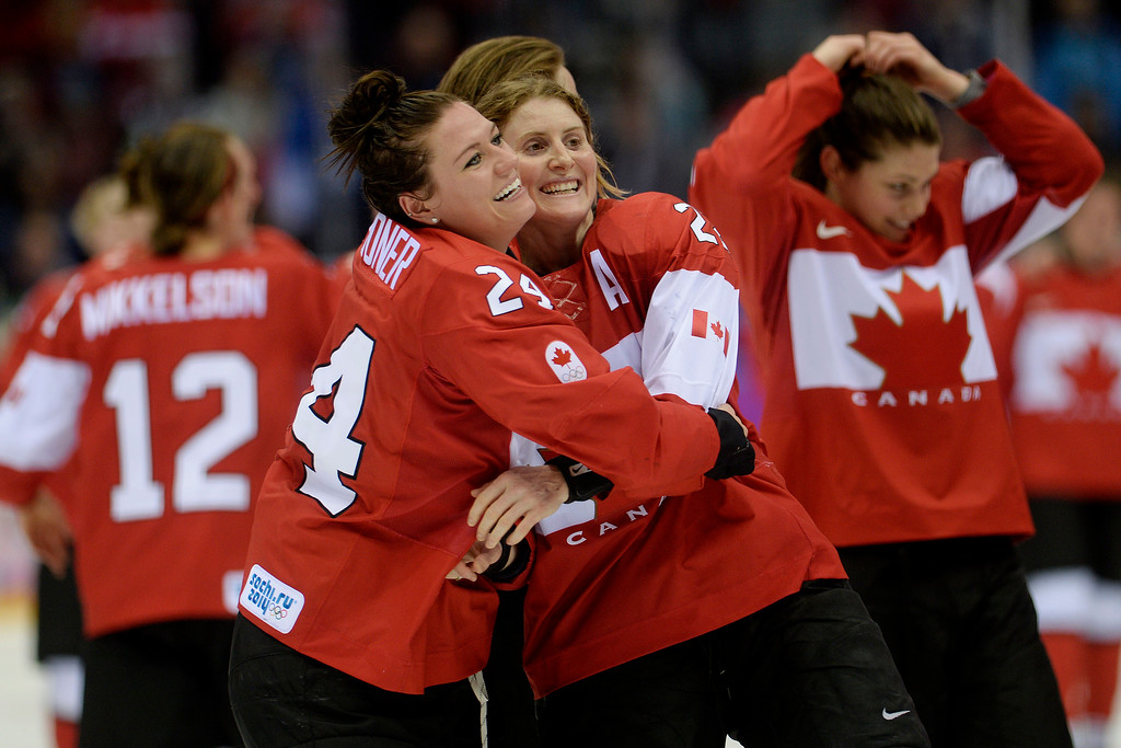 Description of . SOCHI, RUSSIA - FEBRUARY 20: Natalie Spooner (24) of the Canada and Hayley Wickenheiser (22) hug after the overtime period of Canada's 3-2 gold medal ice hockey win over the U.S.A. Sochi 2014 Winter Olympics on Thursday, February 20, 2014 at Bolshoy Ice Arena. (Photo by AAron Ontiveroz/ The Denver Post)