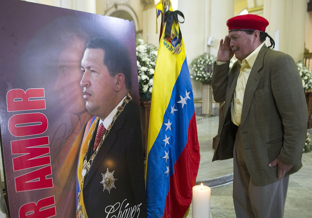 Description of . A man salutes a poster with a picture of the late Venezuelan President Hugo Chavez at Primada Cathedral, on March 8, 2013, in Bogota, during a religious ceremony on behalf of his soul. AFP PHOTO / Raul  ARBOLEDA/AFP/Getty Images