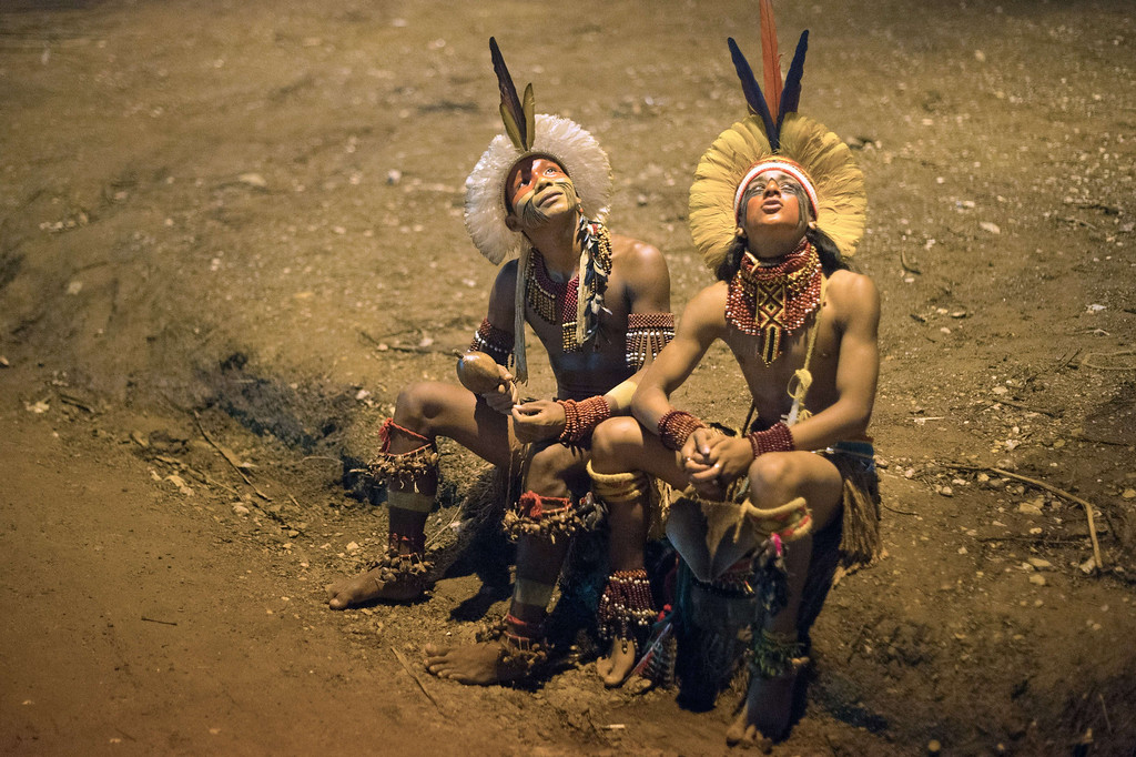 Description of . Brazilian indigenous men of the Pataxo tribe look up after the bow and arrow competition during the XII International Games of Indigenous Peoples in Cuiaba, Mato Grosso state, Brazil on November 12, 2013. AFP PHOTO / Christophe SIMON/AFP/Getty Images