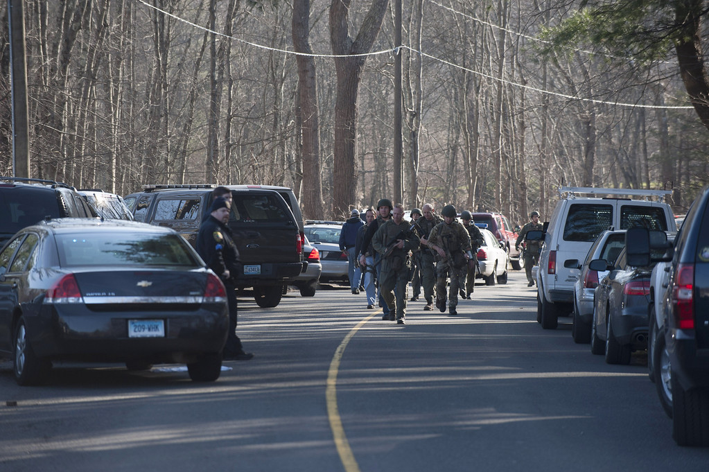 Description of . Connecticut State Police walk on Dickson Street from the scene of an elementary school shooting on December 14, 2012 in Newtown, Connecticut. According to reports, there are more than 20 dead, most children, after a gunman opened fire in at the Sandy Hook Elementary School. The shooter was also killed.  (Photo by Douglas Healey/Getty Images)