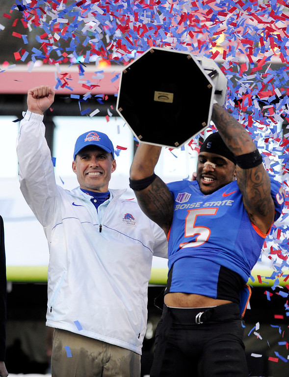 Description of . Boise State coach Chris Peterson, left, gestures as cornerback Jamar Taylor holds the championship trophy after the MAACO Bowl NCAA college football game against Washington, Saturday, Dec. 22, 2012, in Las Vegas. Boise State defeated Washington 28-26. (AP Photo/David Becker)