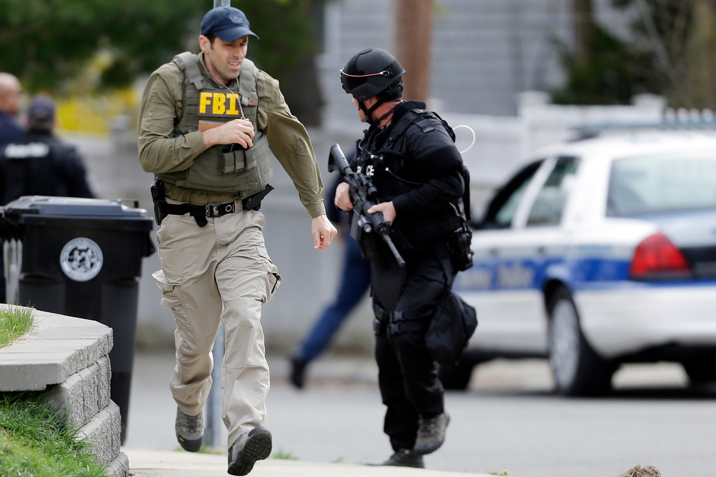 Description of . A police officer and a Federal Bureau of Investigation agent run as they conduct a search for a suspect in the Boston Marathon bombings, Friday, April 19, 2013, in Watertown, Mass.  (AP Photo/Matt Rourke)