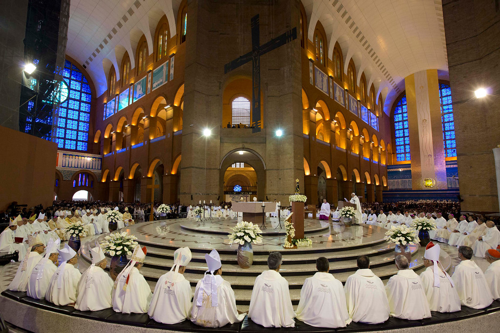 Description of . Members of the clergy listen to Pope Francis, center right, as he gives Mass inside Aparecida Basilica in Aparecida, Brazil, Wednesday, July 24, 2013.  Francis made an emotional plea Wednesday for Roman Catholics to shun materialism in the first public Mass of his initial international trip as pontiff.  (AP Photo/Felipe Dana)