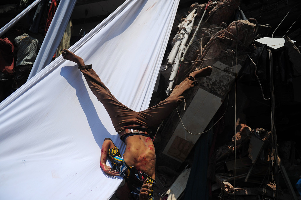 Description of . The dead body of a Bangladeshi garment worker falls after being slid down a length of textile after an eight-story building collapsed in Savar, on the outskirts of Dhaka, on April 24, 2013.  AFP PHOTO/Munir uz  ZAMAN/AFP/Getty Images