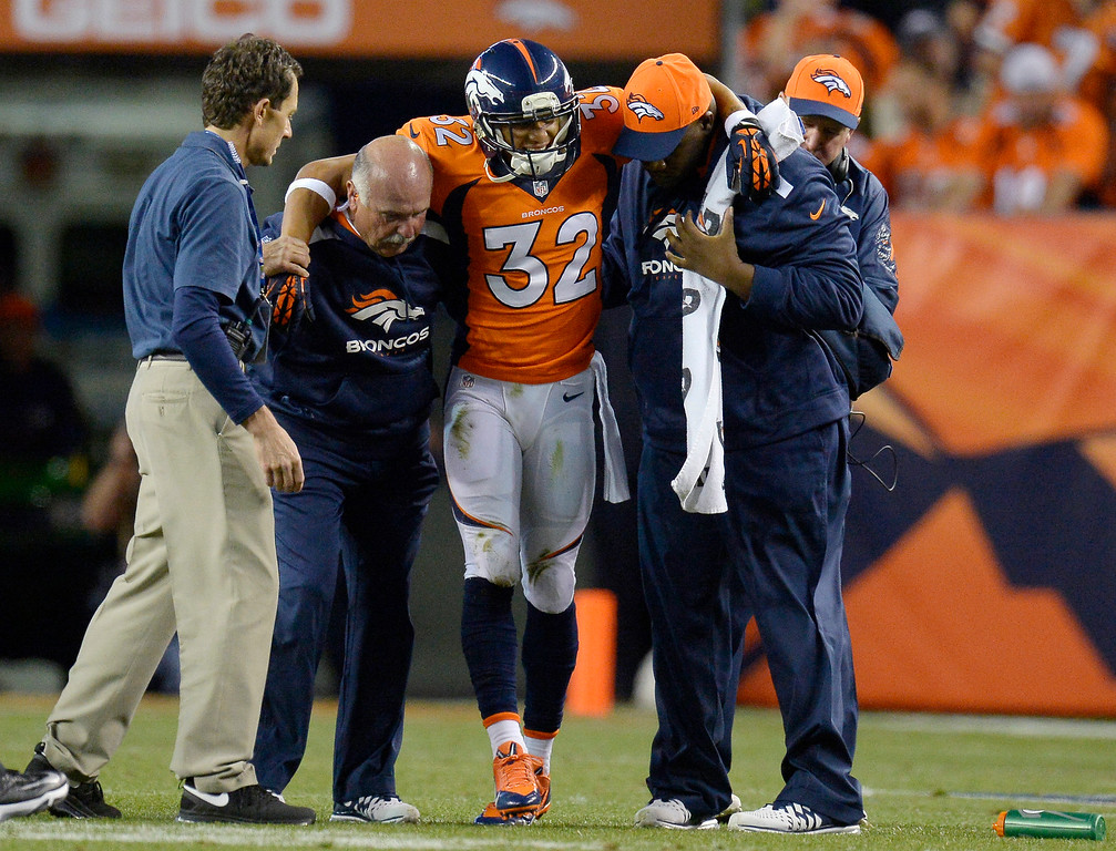 Description of . Denver Broncos defensive back Tony Carter (32) is helped off the field in the first quarter. The Denver Broncos took on the Oakland Raiders at Sports Authority Field at Mile High in Denver on September 23, 2013. (Photo by John Leyba/The Denver Post)
