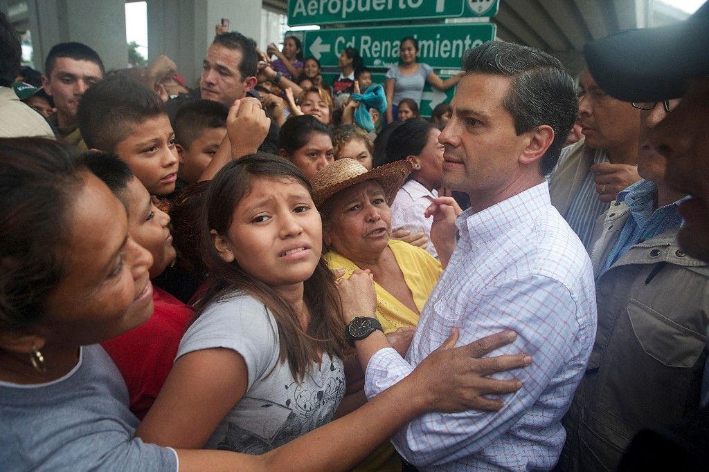 Description of . In this photo released by Mexico's presidential press office, Mexico's President Enrique Pena Nieto meets with people affectedly by Tropical Storm Manuel in the Pacific coast city of Acapulco, Mexico, Monday, Sept. 16, 2013. Pena Nieto toured the disaster zone on Monday and ordered efforts to reopen the highway that connects the port city to Mexico City after twin storms left scenes of havoc on both of Mexico's coasts. (AP Photo/Presidencia de Mexico)