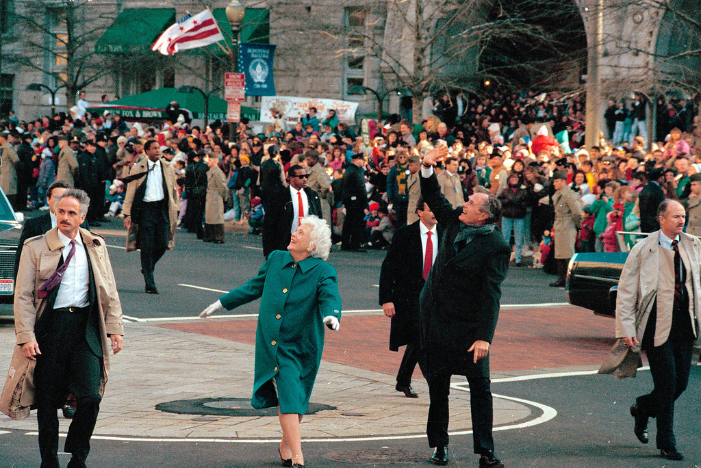 Description of . President George Bush, right, and his wife, first lady Barbara Bush, acknowledge the crowd on Pennsylvania Avenue after getting out of their limousine and walking the inaugural parade route in Washington, D.C., Friday, Jan. 20, 1989. Earlier, Bush was sworn in as the 41st president of the United States. (AP Photo/Dennis Cook)