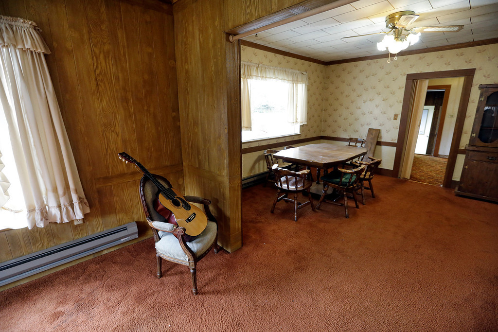 Description of . This photo taken Monday, Sept. 23, 2013, shows a guitar, staged for the home sale, and the dining room table and hutch from when Kurt Cobain, the late frontman of Nirvana, lived there in Aberdeen, Wash. (AP Photo/Elaine Thompson)