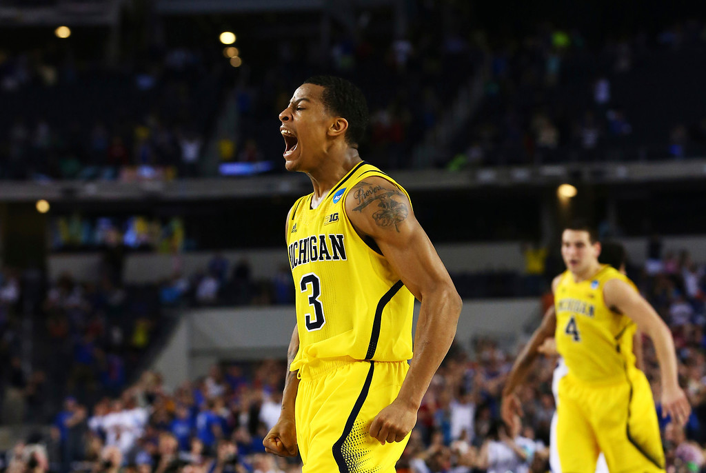 Description of . ARLINGTON, TX - MARCH 29:  Trey Burke #3 of the Michigan Wolverines reacts after shooting a game tying three pointer in the final seconds of the second half againist the Kansas Jayhawks during the South Regional Semifinal round of the 2013 NCAA Men\'s Basketball Tournament at Dallas Cowboys Stadium on March 29, 2013 in Arlington, Texas.  (Photo by Tom Pennington/Getty Images)