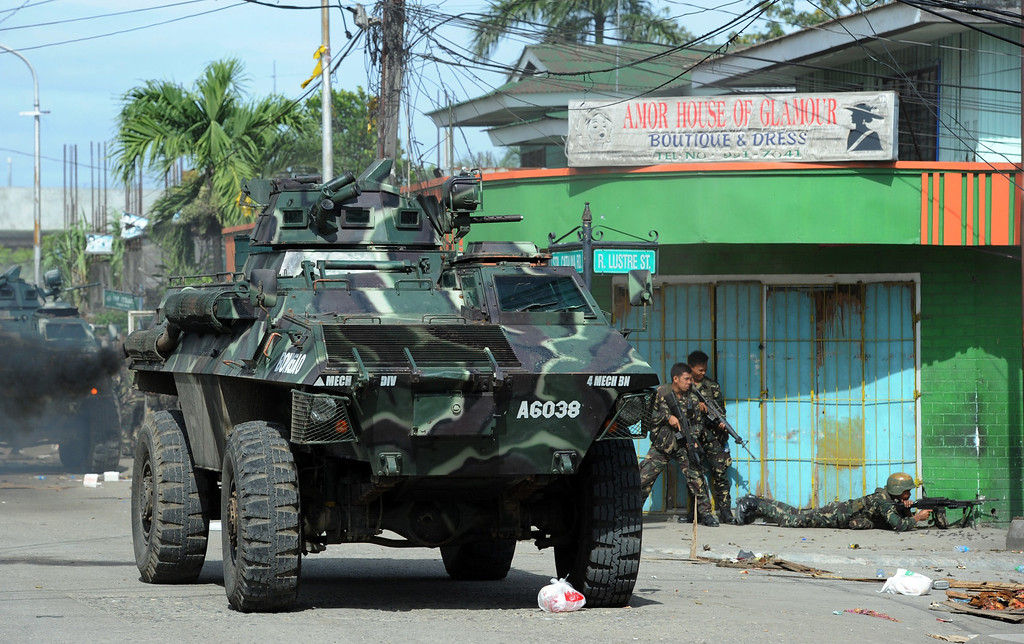 Description of . Philippine soldiers supported by an armored personnel carrier fire towards enemy position during a fire fight between government forces and Muslim rebels as stand-off entered its fourth day in Zamboanga City on the southern island of Mindanao on September 12, 2013. AFP PHOTO/TED ALJIBE/AFP/Getty Images