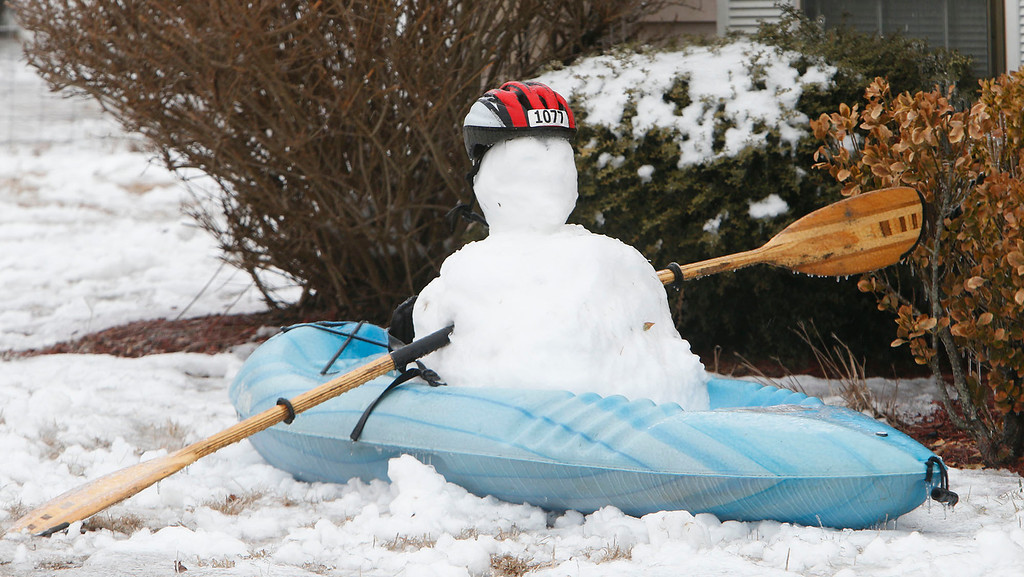 Description of . A kayak snowman is seen in the front yard of a house on U.S. Highway 35, Wednesday, Feb. 12, 2014, in Fort Payne, Ala. Trees and limbs began snapping under the weight of a coat of ice in east Alabama Wednesday, blocking roads during a winter storm that forecasters said could leave as much as a foot of snow in the Tennessee Valley. (AP Photo/Hal Yeager)