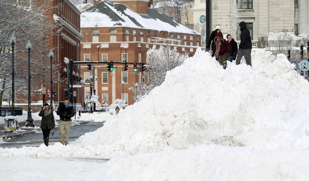 . Johnson & Wales students climb a large pile of snow that was cleared from downtown Providence, R.I., after a winter storm dumped around two feet of snow in the area, Saturday, Feb. 9, 2013. (AP Photo/Stew Milne)