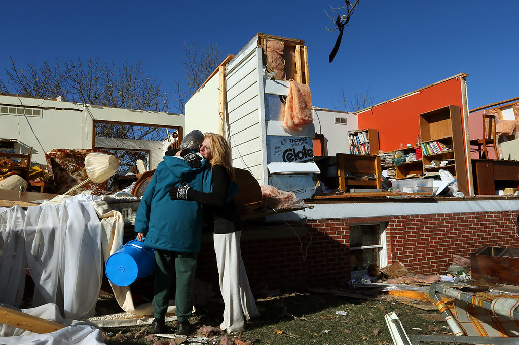 Description of . Rochelle Scott, right, hugs Eunice Hausler while helping her recover her belongings in New Minden, Ill.,    on Monday, Nov. 18, 2013.  Dozens of tornadoes and intense thunderstorms swept across the U.S. Midwest on Sunday, unleashing powerful winds that flattened entire neighborhoods, flipped over cars and uprooted trees. (AP Photo/St. Louis Post-Dispatch, Robert Cohen)