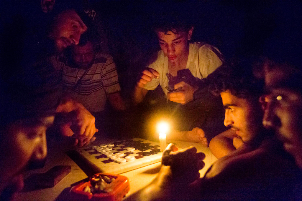 Description of . Syrian rebel fighters play a game by candle light, due to electricity cuts on May 26, 2013 in Adana, near the northeastern city of Deir Ezzor. Syria's opposition denounced as