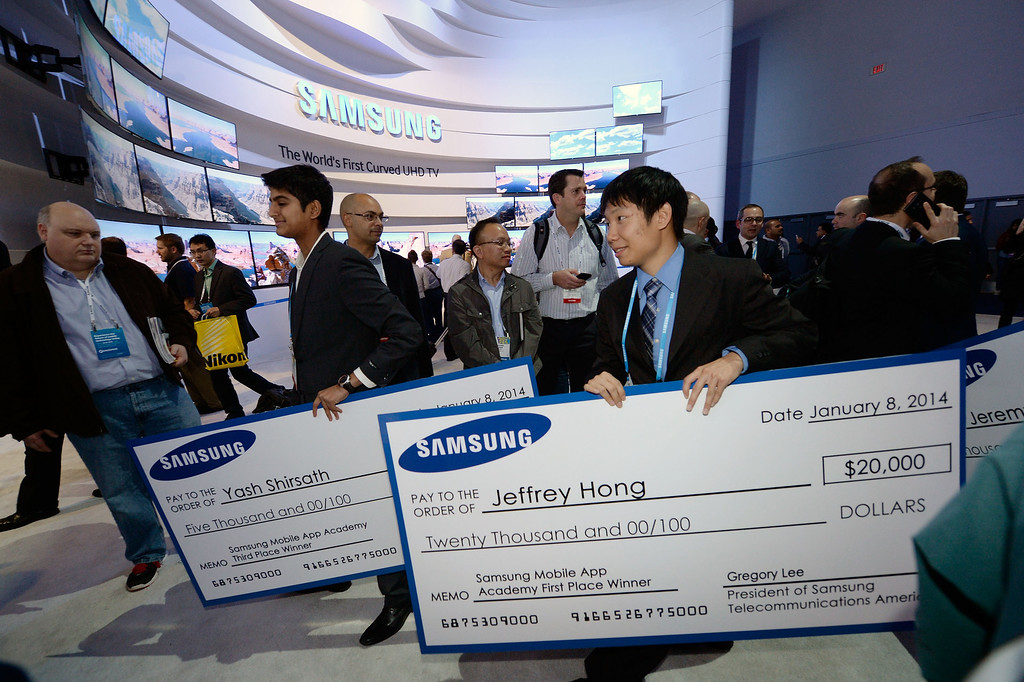 Description of . Samsung Mobile App Academy Scholarship winners Yash Shirsath, left, and Jeffrey Hong walk through the Samsung booth at International CES 2014 on Wednesday, Jan. 8, 2014 in Las Vegas. (Jeff Bottari/AP Images for Samsung)