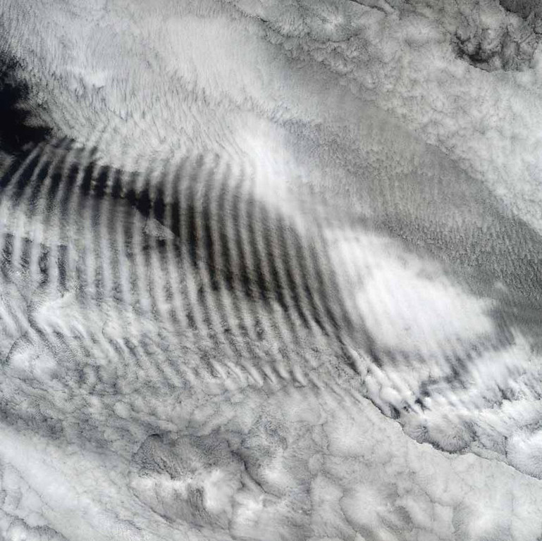 Description of . Gravity Waves, Above the Indian Ocean In this Terra image from 2003, a fingerprint-like feature occurs over a deck of marine stratocumulus clouds. The feature is the result of gravity waves. Similar to the ripples that occur when a pebble is thrown into a still pond, gravity waves sometimes appear when the relatively stable and stratified air masses associated with stratocumulus cloud layers are disturbed by a vertical trigger, such as the underlying terrain, a thunderstorm updraft, or some other vertical wind shear. The stratocumulus cellular clouds that underlie the wave feature are associated with sinking air that is strongly cooled at the level of the cloud tops�such clouds are common over midlatitude oceans when the air is unperturbed by cyclonic or frontal activity.   NASA