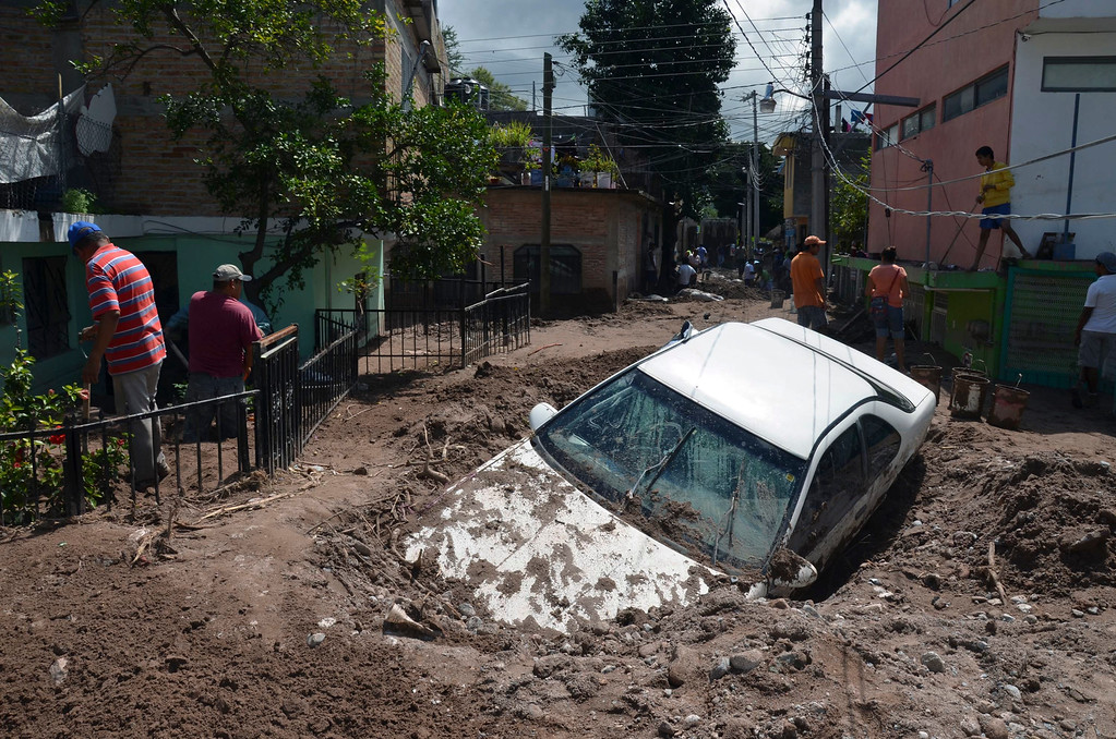 Description of . A car lays buried in mud after flooding triggered by Tropical Storm Manuel as residents try to clean up their neighborhood in Chilpancingo, Mexico, Thursday, Sept. 19, 2013.  Manuel, the same storm that devastated Acapulco, gained hurricane force and rolled into the northern state of Sinaloa on Thursday before starting to weaken. (AP Photo/Alejandrino Gonzalez)