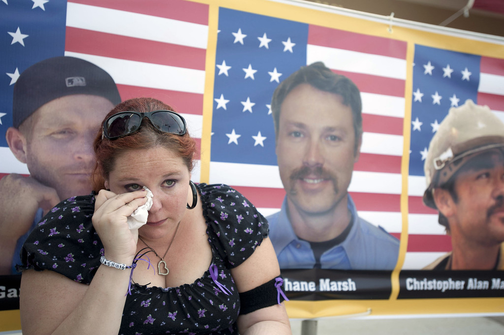 Description of . Laura Marshall, 29, of Phoenix, Arizona sits in front of a photograph of her cousin, Garret Zuppiger (L) who was one of the 19 firefighters killed in a wildfire, at the entrance to a memorial service in their honor at Tim's Toyota Center July 9, 2013 in Prescott Valley, Arizona. (Photo by Laura Segall/Getty Images)