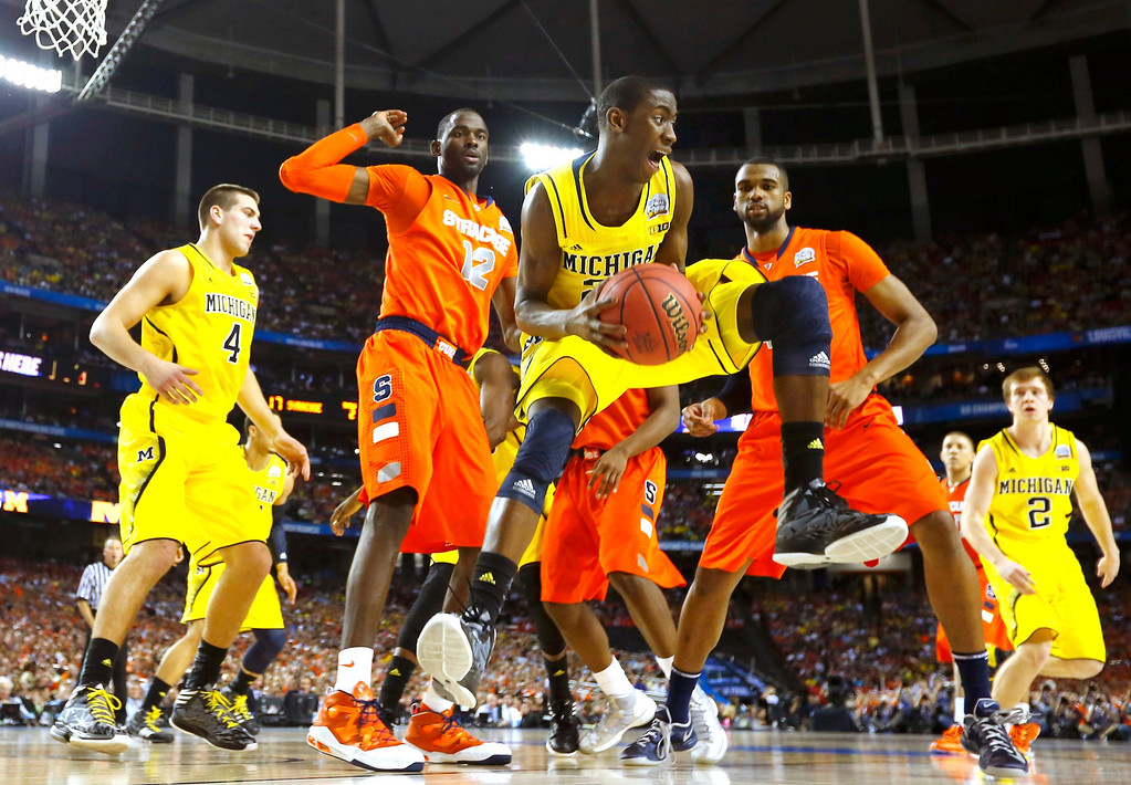 Description of . Michigan Wolverines guard Caris LeVert (23) pulls in a rebound against the Syracuse Orange in the first half of their NCAA men's Final Four basketball game in Atlanta, Georgia April 6, 2013. REUTERS/Jeff Haynes