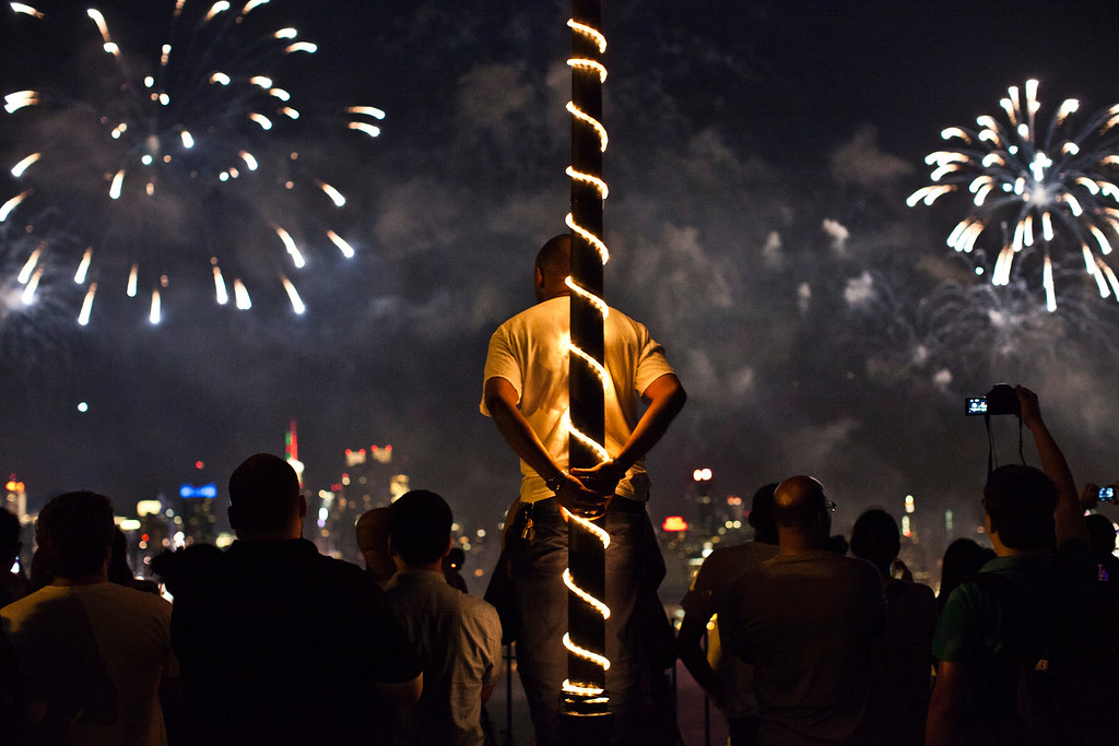 Description of . WEEHAWKEN, NJ - JULY 4: People watch fireworks light up the sky over New York City on July 4, 2013 in Weehawken, New Jersey. July 4th is a national holiday with the nation celebrating its 238th birthday.  (Photo by Kena Betancur/Getty Images)